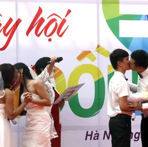 Same-sex couples kiss during their public wedding as part of a LGBT event on a street in Hanoi
