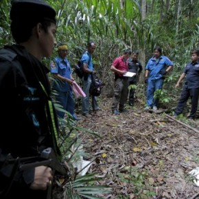 Security forces and rescue workers inspect a mass grave at a rubber plantation near a mountain in Thailand's southern Songkhla province May 7, 2015.  REUTERS/Surapan Boonthanom
